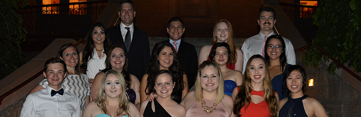 students dressed up on the steps outside of the spring formal